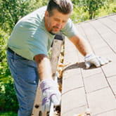Man cleaning roof gutters photo