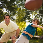 Father and son throwing football photo